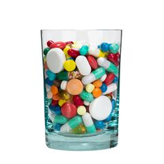 Medical cocktail - glass full of pills. Isolated